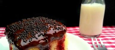 Poke cake de baunilha com geleia de frutas vermelhas e cobertura de chocolate amargo