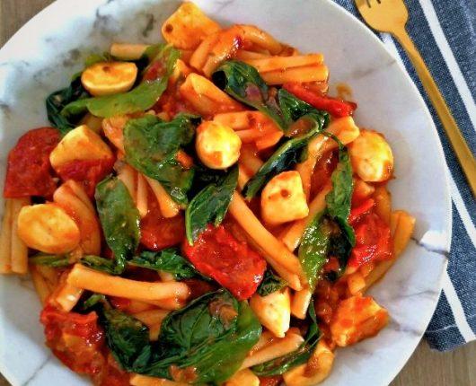 Macarrão caprese com muçarela, rúcula e tomate seco
