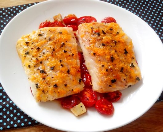 Filé de peixe com queijo e manjericão sobre tomatinhos assados
